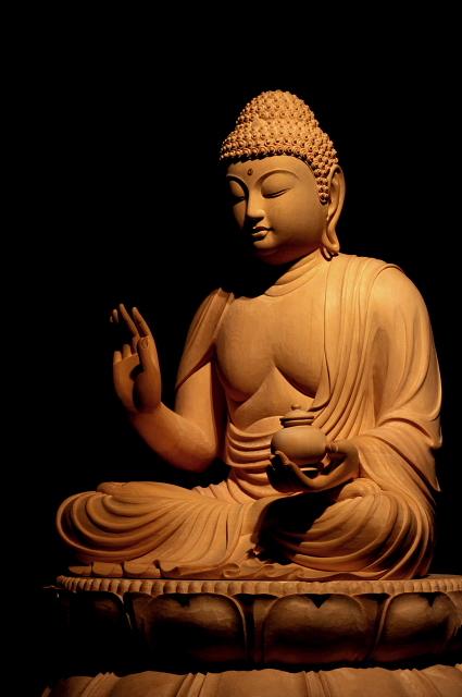 仏像彫刻原田謹刻 薬師如来坐像 東方浄瑠璃世界の教主。衆生(しゆじよう)の病気を治し,安楽を得させる仏。仏教の伝来以後,治病の仏として広く信仰されている。薬壺を持つ像が多い。日光・月光(がつこう)の両菩薩を脇侍とし,十二神将を眷属(けんぞく)とする。薬師瑠璃光如来、薬師仏、大医王仏とも呼ばれる。