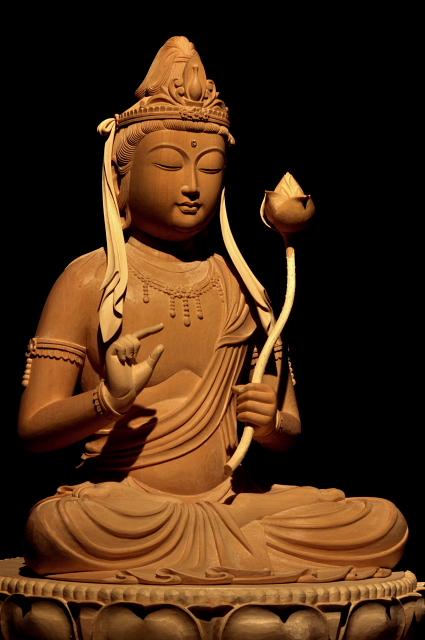 仏像彫刻原田謹刻 勢至菩薩坐像 智慧の光により菩薩心の種子を与え、その光によって衆生を救う菩薩。うま年の守り本尊、十三仏の一周忌本尊として知られている。観音菩薩が宝冠の前面に化仏を表すのと対照的に、勢至菩薩は水瓶を付けることが多い。 ◆このお姿は半眼で、左手に持たれた未敷蓮華(ハスの蕾)を、右手で開花させようとする印相をとっておられます。