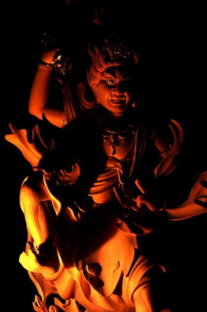 仏像彫刻原田謹刻 蔵王権現像(ざおうごんげんぞう) 【蔵王権現】修験道の本尊。正式名称は金剛蔵王権現(こんごうざおうごんげん)。インドに起源を持たない日本独自の仏で、奈良県吉野町の金峯山寺本堂(蔵王堂)の本尊として知られる。 役小角が、吉野の金峯山で修業中に示現したという伝承があり、釈迦如来、千手観音、弥勒菩薩の三尊の合体したものとされる。「金剛蔵王」とは究極不滅の真理を体現し、あらゆるものを司る王という意。権現とは「権(かり)の姿で現れた神仏」の意。 右手に持った法具で天魔を粉砕し、左手の印で一切の情欲や煩悩を断ち切る。左足の踏みつけは地下の悪魔を押さえつけ、右足の蹴り上げで天地間の悪魔を払っている。背後の炎は大智慧をあらわす。