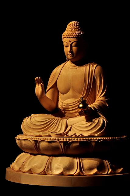 仏像彫刻原田謹刻  薬師瑠璃光如来坐像(やくしるりこうにょらいざぞう) 【薬師瑠璃光如来】 東方浄瑠璃世界の教主。 人々を病の苦しみから救い、寿命を延ばし、貧困を除く。 薬師様は、まだ菩薩として修行しておられた時に衆生を救済する十二の大願を立てられ、それを成就されて如来になられました。薬師様には、病からの救済のほか、古くは罪を懺悔(さんげ)する修法の本尊として、また、天変地異や政変などの社会不安からの救済という大きな願いが託されてきました。左手には万病に効く薬が入った薬壺(やっこ)を持たれています。「薬師」とは、外科が存在しなかった中世以前には、現代の医師に対応する言葉であったそうです。