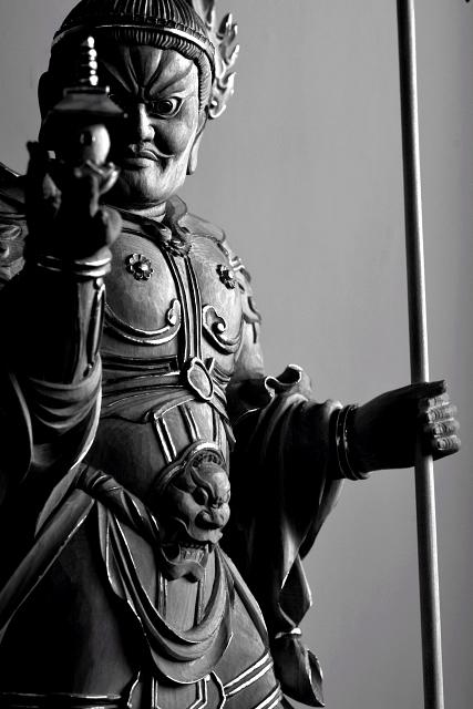 仏像彫刻原田謹刻 毘沙門天立像(びしゃもんてんりゅうぞう) 【毘沙門天】 サンスクリット名ヴァイシュラヴァナを音写したもので多聞天とも訳す。古代インド神話中のクベーラ(地下に埋蔵されている財宝の守護神であり、北方の守護神とされる。)が仏教にとり入れられた。四天王の一尊として北方をつかさどり,また財宝富貴をも守るといわれる。形像は,甲冑を着る武神像で,掌上に宝塔をのせ,もう一方の手に宝棒または鉾を執り、邪鬼の上に乗る姿が一般的である。仏教では、吉祥天の夫とされる。四天王中最強で財宝の神として独立して信仰されている。