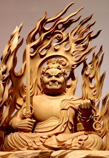 仏像彫刻原田謹刻 不動明王坐像(ふどうみょうおうざぞう) 【不動明王】 悪を降(くだ)し、衆生(しゅじょう)を守る。仏道に導きがたいものを畏怖せしめ、煩悩を打ちくだく。菩提心の揺るがないことから不動という。大日如来の化身として、すべての悪と煩悩をおさえしずめ、生あるものをすくう。岩上に座して火炎に包まれた姿で、怒りの形相に表す。右手に悪をたちきる剣を、左手に救済の索を持つ。サンスクリット名アチャラナータAcalanāthaの漢訳で、発音に従い阿遮羅囊他と記す場合もある。 ◆このお姿は、一般在家のお客様からのご注文で納入させていただいたお姿です。御面相や体躯、光背の形状などは、お客様がお持ちの複数のお写真を基に、ご希望を伺った上で謹刻させていただきました。