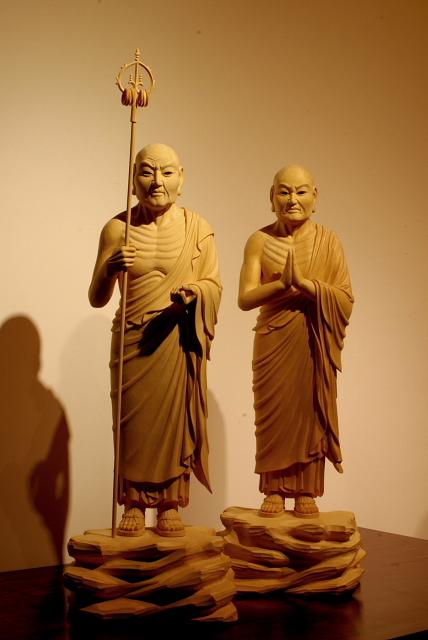 仏像彫刻原田謹刻  釈迦十大弟子像うち 迦葉尊者像 阿難尊者像 【釈迦十大弟子】 お釈迦様の弟子の中で主要な10人の弟子のこと。 【迦葉尊者~かしょうそんじゃ】 釈迦十大弟子の一人。パーリ語でマハーカッサパ、サンスクリット語でマハーカーシャパ。仏教教団でお釈迦様の後継(第2祖)とされ、お釈迦様の死後、第一結集の座長を務めた。頭陀第一といわれ、衣食住にとらわれず、清貧の修行を行った。 【阿難尊者~あなんそんじゃ】 釈迦十大弟子の一人。パーリ語でも、サンスクリット語でアーナンダ。多聞第一といわれ、お釈迦様の従弟。出家して以来、お釈迦様が亡くなるまで25年間付き人をした。第一結集のとき阿難尊者の記憶に基づいて経が編纂された。 【結集~けつじゅう】 「結集」のサンスクリット語の本来の意味は「ともに歌うこと」であった。比丘たちが集まってお釈迦様の教えを誦出(じゅしゅつ)し、互いの記憶を確認しながら、合議のうえで仏典を編集した事業を結集と呼んでいる。伝承によると、お釈迦様入滅後、王舎城郊外に500人の比丘(すなわち、五百羅漢)が集まり、最初の結集が開かれたという。このときは、迦葉尊者が座長となり、阿難尊者と優波離尊者が、それぞれ経(経典)と律(戒律)の編集責任者となった。
