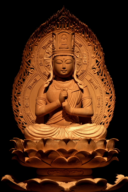 仏像彫刻原田謹刻 ひつじ年守り本尊 大日如来像(だいにちにょらいぞう) 【大日如来】 大日とは「偉大な輝くもの」を意味し、元は太陽の光照のことでしたが、のちに宇宙の根本の仏の呼称となりました。真言密教の教主であり、諸仏・諸菩薩の根元をなす理智体で,宇宙の実相を仏格化した根本仏とされます。常に「生きる力」を授け、精一杯生きる私たちを見守り続けていてくださいます。