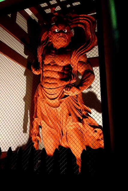 仏像彫刻原田謹刻 仁王像(におうぞう)総高5㍍ 【仁王】 仏教の守護神。サンスクリットではヴァジュラダラと言い、「金剛杵(こんごうしょ、仏敵を退散させる武器)を持つもの」を意味します。二王ともかき,金剛神・金剛力士とも呼ばれ、山門の左右に安置され、仏法僧を守護するのがお役目です。元来はインド神話の神で,武装姿もありますが,日本では裸姿の力士像がほとんどのようです。向かって右は金剛杵(しょ)をもち口をあけた阿形(あぎょう)で,左は口をとじた吽形(うんぎょう)となります。そのルーツをたどるとギリシア神話の英雄ヘラクレスに行きあたります。