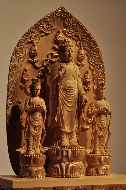 仏像彫刻原田謹刻 一光三尊阿弥陀如来像 【善光寺式阿弥陀三尊】 阿弥陀如来を中尊に,その左右に観音、勢至の二菩薩を脇侍とする。三尊全体の背後を大きな一枚の舟形光背がおおっている。これにより「一光三尊」という。この一光三尊形式の源流は中国北魏時代の仏像に求められる。三尊足下の蓮台は臼形蓮台とよばれ,蓮肉部の高い垂敷蓮華である。光背は大きな舟形光背で,光中に七化仏がある。 ◆お施主様からのご要望で、総高45㎝のお姿を謹刻納入させていただきました。桧の白木素地に、金線が施してございます。