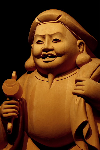 仏像彫刻原田謹刻 大黒天像 【大黒天】 仏法の守護神。 元来はヒンズー教の神で、密教では大自在天の化身。サンスクリットでマハーカーラ。日本では大国主命と習合し、頭巾をかぶり、袋を背負い、打ち出の小槌をもつ福の神として七福神の一神となる。 ◆ご寺院様に伝わる既存のお姿(総高30㎝)を基本とし、総高115㎝にて謹刻させていただきました。