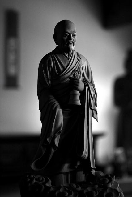 仏像彫刻原田謹刻 普化禅師像(ふけぜんじぞう) 【普化禅師】 中国、唐代の禅僧。普化宗の開祖。盤山宝積(ばんざんほうしゃく)より法を受けたが、あたかも狂僧のごとくふるまい、師の寂後は北地に遊んだ。常に手には一鐸を持ち、振鐸して人々を教化し、行雲流水の如く道を歩んだ。そんな禅師の姿を敬慕する、河南府から鎮州に来た張伯居士がいた。張伯は禅師の徳を敬い、振鐸の音に惚れこんでいた。ある日彼は禅師の前に来て弟子入りを請うたが、断られた。しかし張伯はあきらめず、自分の好む竹管で常に禅師の振鐸の音色を真似してほかの曲を吹かず、自ら虚鐸と号した。普化宗は建長年間(1249~1256)日本に伝来。江戸時代に栄え、宗徒は虚無僧と称して尺八を奏し、諸国を遍歴修行した。 ◆山形市臥龍会様よりご用命をいただき謹刻させていただきました。