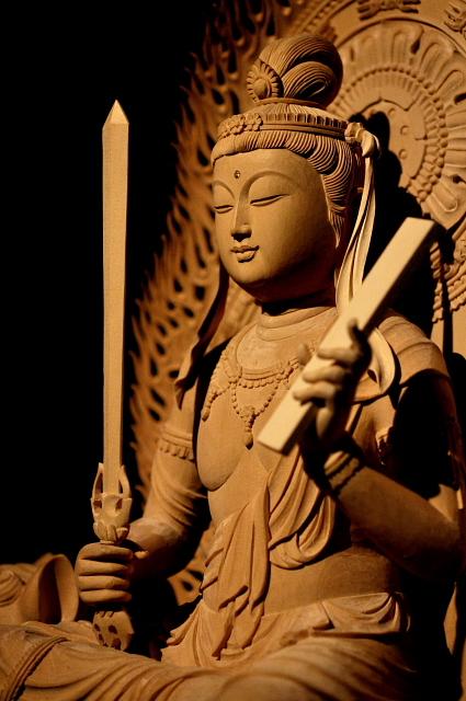 仏像彫刻原田謹刻 文殊菩薩像(もんじゅぼさつぞう) 【文殊菩薩】 文殊は梵名Mañjuśrī(マンジュシュリー)の音写、文殊師利(もんじゅしゅり)の略称である。 智慧をつかさどる菩薩。普賢菩薩とともに諸菩薩の上位に位置し釈迦に侍す。一般に右手に剣、左手に経巻をもち、獅子に乗る姿であらわされる。卯年の守り本尊。 【三人寄れば文殊の智恵】 文殊菩薩の徳性は悟りへ到る重要な要素、般若(智慧)であるが、本来悟りへ到るための智慧という側面の延長線上として、一般的な知恵(頭の良さや知識が優れること)の象徴ともなり、これが後に「三人寄れば文殊の智恵」ということわざを生むことになった。 【般若】 サンスクリット語のprajñā(プラジュニャー)パーリ語paññā(パンニャーの音写語。慧(え)と漢訳される。『悟りを得るための真実の智慧』あるいは、『あらゆるものごとを見通す見識』を意図している。
