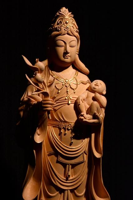 仏像彫刻原田謹刻 鬼子母神像(きしもじんぞう) 【鬼子母神】 仏法を守護する善女神。安産や育児の神。法華経護持の神ともされる。天女の姿をとり、左手に一子を抱き、右手には吉祥果を捧げる。ときには鬼神形のものもある。千人の子があったが、他人の子を取って食い殺したため、釈尊はその最愛の一児を隠してこれを教化し、のち仏に帰依して出産・育児の神となった。きしぼじん。訶梨帝母(かりていも)。ハーリティー。 【吉祥果】 鬼子母神が手に持つ魔除けの果実。なお吉祥果をザクロで表現するのは中国文化での影響であり、これは仏典が漢訳されたときに吉祥果の正体が分からなかったため、ザクロで代用表現したものである。