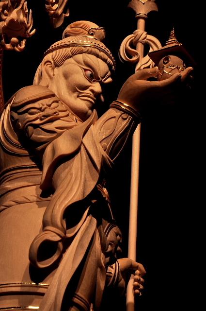 仏像彫刻原田謹刻 毘沙門天像 サンスクリット名ヴァイシュラヴァナ(Vaiśravaṇa)を写したもので多聞天とも訳す。古代インド神話中のクベラ(Kuvera,俱尾羅 ガンジス河のワニを神格化した神)が仏教にとり入れられた。拘毘羅(くびら)毘沙門と称されることもある。四天王の一尊として北方をつかさどり,また財宝富貴をも守るといわれる。形像は,甲冑を着る武神像で,一方の掌に宝塔をのせ,もう一方の手に戟または宝棒を持ち2邪鬼の上に乗る姿が一般的である。吉祥天は毘沙門天の妻である。