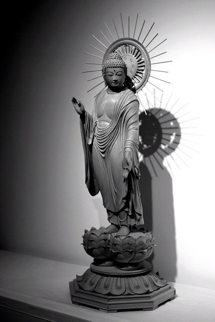 仏像彫刻原田謹刻 見返り阿弥陀像(みかえりあみだぞう) 【見返り阿弥陀】 京都市左京区にある通称永観堂(えいかんどう)の名で知られる禅林寺の本尊阿弥陀如来立像は、顔を左に曲げた特異な姿の像である。この像については次のような伝承がある。永保2年(1082年)、当時50歳の永観(ようかん)が日課の念仏を唱えつつ、阿弥陀如来の周囲を行道していたところ、阿弥陀如来が須弥壇から下り、永観と一緒に行道を始めた。驚いた永観が歩みを止めると、阿弥陀如来は振り返って一言、「永観遅し」と言ったという。本寺の阿弥陀如来像はそれ以来首の向きが元に戻らず、そのままの姿で安置されているのだという。 ◆上記の伝承に基づき、御寺院様の御用命で謹刻させて頂きました。