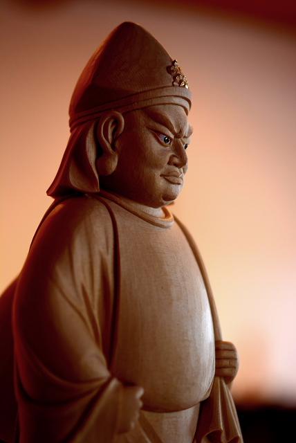 仏像彫刻原田謹刻 大黒天像(だいこくてんぞう) 【大黒天】 元来はヒンズー教の神で、密教では大自在天の化身である。サンスクリット語のマハーカーラの訳で、摩訶迦羅と音写する。マハーカーラは偉大な黒い神、偉大な時間=破壊者を意味する。マハーとは大もしくは偉大なる、カーラとは時あるいは黒を意味する。三宝を守護し、戦闘をつかさどり、飲食を豊かにする神で黒色忿怒相を示す。中国南部では金袋を持ち腰掛ける姿となり、諸寺の厨房に祀られた。わが国の大黒天はこの系統で、最澄によってもたらされ、天台宗の寺院を中心に祀られたのがその始まりといわれる。その後、台所の守護神から福の神としての色彩を強め、七福神の一つとなり、頭巾をかぶり左肩に大袋を背負い、右手に小槌を持って米俵を踏まえるといった現在よくみられる姿になる。音韻や容姿の類似から大国主命と重ねて受け入れられ、商売繁盛を願う商家はもとより、農家においても田の神として信仰を集めている。