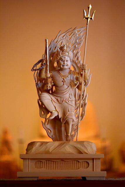 仏像彫刻原田謹刻 烏枢沙摩明王像(うすさまみょうおうぞう) 【烏枢沙摩明王】 人間界と仏の世界を隔てる天界の「火生三昧」(かしょうざんまい)と呼ばれる炎の世界に住し、人間界の煩悩が仏の世界へ波及しないよう聖なる炎によって煩悩や欲望を焼き尽くす反面、仏の教えを素直に信じない民衆を何としても救わんとする慈悲の怒りを以て人々を目覚めさせようとする明王である。古代インド神話において元の名を「ウッチュシュマ」、或いは「アグニ」と呼ばれた炎の神であり、「この世の一切の汚れを焼き尽くす」功徳を持ち、仏教に包括された後も「烈火で不浄を清浄と化す」神力を持つことから、心の浄化はもとより日々の生活のあらゆる現実的な不浄を清める功徳があるとする。意訳から「不浄潔金剛」や「火頭金剛」とも呼ばれた。現在でも寺院の東司で祀られている。