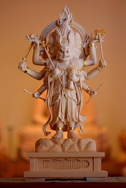 仏像彫刻原田謹刻 三宝荒神像(さんぽうこうじんぞう) 【三宝荒神】 日本特有の仏神。仏法僧の三宝を守護し、不浄や災難を除去する。火と竈の神として信仰され、かまど神として祭られることが多い。 【真言 ~ オン ケンバヤ ケンバヤ ソワカ】 三宝荒神は、神仏習合を背景としながら、日天の眷属である地震を司る神である「剣婆」(けんばや)と同一視された。「剣婆」はサンスクリット語のKampa(地震波)を語源に持つ。 【綾子~あやつこ】 子供の「お宮参り」の時に、鍋墨(なべずみ)や紅などで、額に「×」、「犬」と書くこと言う。魔よけの印で、イヌの子は良く育つということに由来するとされ、全国的にでは無いが、地方によって行われる所がある。古文献によると、この「あやつこ(綾子)」は紅で書いたとある、だが紅は都の上流階級でのみ使われたことから、一般の庶民は「すみ」、それも「なべずみ」で書くのが決まりであったという。この「なべずみ」を額に付けることは、家の神としての荒神の庇護を受けていることの印であった。東北地方で、この印を書くことを「やすこ」を書くと言う。宮参りのみでなく、神事に参列する稚児が同様の印を付ける例がある。「あやつこ(綾子)」を付けたものは、神の保護を受けたものであることを明示し、それに触れることを禁じたのであった。のちには子供の事故防止のおまじないとして汎用されている。